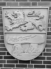 Wappen vom Landkreis Heidekreis an der Fassade des Verwaltungsgebäudes in Soltau; das Wappen setzt sich zusammen aus dem Löwen des  Herzogtums Braunschweig-Lüneburg und einer Abbildung der Hünengräber der Sieben Steinhäuser.