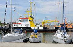 Sportboote / Segelboote im Fluthafen von Wilhelmshaven; dahinter das Arbeitsschiff / Mehrzweckschiff Rüstersiel.  Das Schiff wird vom Wasserstraßen- und Schifffahrtsamt Wilhelmshaven für die Kontrolle und Versorgung feststehender Seezeichen-