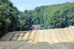 Abgeerntete Felder beim Weyerberg in Worpswede - Dach eines kleinen Wohnhauses am Waldesrand.