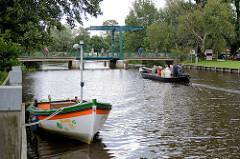 Lauf der Hamme durch das Teufelsmoor in Worpswede, im Hintergrund die Klappbrücke über den Fluss; ein alter Torfkahn fährt unter Motor zu seinem Liegeplatz.