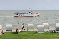 Ausflugschiff / Fahrgeschäft Etta v. Dangast vor dem Südstrand in Wilhelmshaven; weiße Strandkörbe stehen hinter dem Deich.