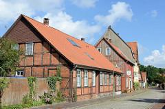 Historisches Fachwerkgebäude / Wohnhaus, blühender Rosenstrauch am Holzzaun - dahinter das Gebäude der alten Schützenstuben in der Rosenstraße von Soltau.