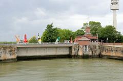 Ehemalige Signalstation in Wilhelmshaven an der jetzt geschlossenen 1. Einfahrt zum Hafen; das Denkmal geschützte Gebäude wurde 1886 gebaut - dahinter der neue Radarturm.