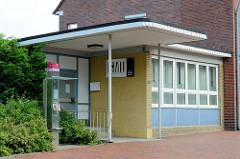 Kleiner Anbau im Architekturstil der 1960er Jahre mit vorspringend Dach und gelber Ziegel Fassade..