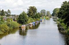 Bootssteg mit kleinen Motorbooten und am Ufer der Hamme Schrebergärten - im Hintergrund die Teufelsmoorschleuse.