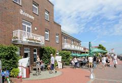 Südstrandpromenade in Wilhelmshaven, außen Gastronomie mit Tischen unter Sonnenschirmen; Backsteingebäude als Hotel und Restaurant.