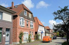 Wohnhäuser in unterschiedlichem Baustil, Rosenstauden an den Hausfassaden, Straße mit Kopfsteinpflaster;  Rosenstraße in Soltau.