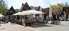 Am Markt von Soltau - rekonstruierte historische Einzelhäuser mit  Geschäften, links der  Heirats Brrunnen - auf dem Platz ein Eiscafe mit Sonnenschirmen und Tischen in der Sonne.