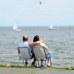 Touristen am Ufer der Nordsee in Wilhelmshaven; ein Paar sitzt auf Campingstühlen und blickt auf Segelschiffe auf dem Meer.