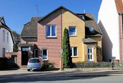 Doppelhaus mit unterschiedlicher Fassadengestaltung - verschiedene Ziegelfarben und Vorgarten.