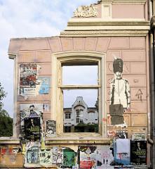 Hausruine - Restwand mit Fensterhöhle eines Gründerzeitgebäudes in Hamburg St. Pauli - die Hausfassade ist mit Veranstaltungsplakaten / Graffiti versehen.