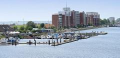 Mehrstöckige Neubauten mit Ferienwohnungen am Südstrand / großer Hafen von Wilhelmshaven; davor Bootsstege mit Sportbooten.
