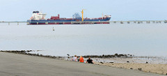 Blick zum Ölhafen in Wilhelmshaven, ein Tanker hat am Anleger festgemacht; eine Pipeline führt auf Stelzen über das Wasser. Badegäste  / Touristen sitzen am befestigten Asphaltweg am Ufer der Nordsee und blicken auf Wasser.