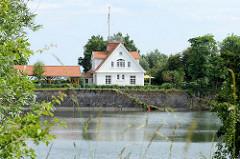 Blick über die ehemalige zweite Einfahrt von der Nordsee in den Ems Jade Kanal von Wilhelmshaven. Hinter einer alten Kaimauer mit Wassertreppe steht ein neues Einfamilienhaus mit Carport.