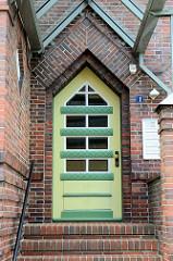 Eingangstür eines expressionistischen Gebäudes in Soltau / Verwaltungsgebäude des Feuerversicherungsverein Soltau a.G; Backsteinarchitektur mit ummauerten Haus Eingang und spitzzulaufender  Tür.