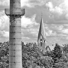 Fabrikschornstein der  Soltauer Filzfabrik Gebr. Röders AG - zwischen Bäumen der Kirchturm der Soltauer Lutherkirche.