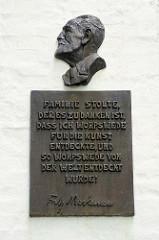 Bronzeplakette mit dem Porträt von Fritz Mackensen an der Hauswand vom Gebäude des Stolte-Haus /Kaufhaus in der  Findorffstraße von Worpswede - der Künstler  Fritz Mackensen lebte dort ab 1884.