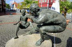 Bronzeskulpturen an der Marktstraße in Soltau - Kunst im öffentlichen Raum;  eine dicke Figur / dicker Mann hilft einem Dünnen und sichert ihn gegen den Absturz vom Stein, Findling.