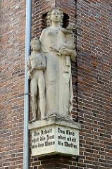 Eckskulptur Mutter mit Kindern an einem Gebäude in Wilhelmshaven; Inschrift: die Arbeit ehrt die Frau wie den Mann - das Kind aber adelt die Mutter.