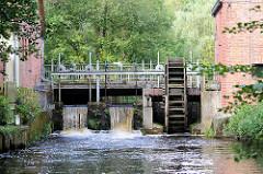 Blick über den Fluss Böhme zum Stauwerk Wasserrad der alten Waldmühle am Mühlenweg in Soltau.