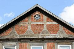 Giebel eines historischen Fachwerkhauses am Bahnhof in Soltau; rundes Metallfenster in Ziegeln eingefasst, Schnitzereien in Fachwerkbalken - Sinnspruch im Stützbalken: an Gottes Segen ist alles gelegen.