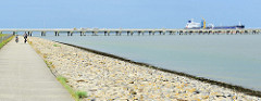 Blick zum Ölhafen in Wilhelmshaven, ein Tanker hat am Anleger festgemacht; eine Pipeline führt auf Stelzen über das Wasser. Zwei Radfahrer fahren auf dem Fahrradweg entlang des Nordseeufers.