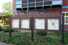 Bekanntmachungen der Stadt Soltau mit Wappen / Holzschnitzerei über Informationsvitrinen am neuen Soltauer Rathaus.