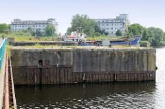 Schleusenreste der ehemaligen zweiten Einfahrt zum Ems Jade Kanal / Hafen in Wilhelmshaven. Im Hintergrund die Gebäude der ehemaligen Lagerhäuser für Minen und Torpedos in der Schleusensstraße.