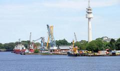 Arbeitsschiffe und Kräne im Hafen / Ems Jade Kanal von Wilhelmshaven - im Hintergrund der 114 Meter hohe Radarturm, der 1977 errichtet wurde.