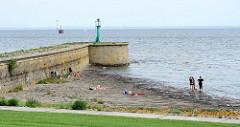 Mole mit Leuchtfeuer / Leitfeuer am Hafen von Wilhelmshaven; Badegäste haben ihre Handtücher auf den Steinen der Uferbefestigung ausgebreitet.