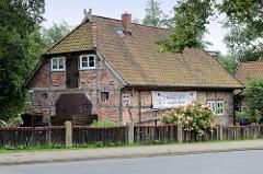 Historische Fachwerkscheune mit Holzzaun und blühenden Hortensien in der Bahnhofstraße von Soltau.
