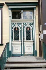 Alte Eingangstür / Doppeltür eines Wohnhauses in der Feldstraße von Soltau. Aufwändige Schnitzereien, weiß abgesetzt - vergittertes Fenster im Jugendstil mit Blüte.