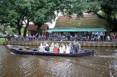 Ein Torfkahn mit Touristen an Bord fährt auf seiner Rundfahrt durch das Teufelsmoor auf der Hamme bei Worpswede; am Ufer ein Café / Restaurant mit Biergarten.