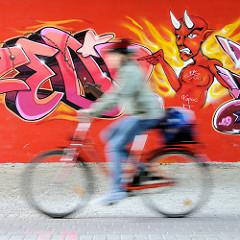 Graffiti mit Teufel - zeigt auf einen Fahrradfahrer; Fussgängerunterführung unter Wilhelmburger Reichsstraße im Hamburger Stadtteil Wilhelmsburg.
