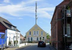 Blick zum alten Postamt von Burhave, erbaut 1871 - hoher Sendemast für Telekommunikation.
