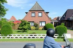 Einzelhaus mit Krüppelwalmdach, symmetrischer Hausfront;  Vorgarten / Rasen mit Steinzaun.