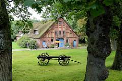 Reetgedecktes Bauernhaus mit ziegelverzierten Giebel, Tenne und Wohnbereich mit Dachausbau, errichtet 1904 - jetzt Nutzung als Einrichtungshaus. Zwischen den Bäumen steht ein alter Holzkarren mit großen Holzrädern und Deichsel auf der Wiese..