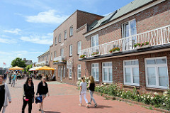 Südstrandpromenade in Wilhelmshaven, Außengastronomie  mit Tischen unter Sonnenschirmen; Backsteingebäude als Hotel und Restaurant.