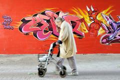 Graffiti mit Teufel - zeigt auf eine älter Frau mit Gehwagen; Fussgängerunterführung unter Wilhelmburger Reichsstraße im Hamburger Stadtteil Wilhelmsburg.