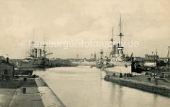 Historische Aufnahme vom Hafen in Wilhelmshaven - Kriegsschiffe mit hohem Schornstein / Dampfer liegen am Kai.