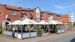 Kaufhaus / Ladenzeile mit Außengastronomie an der Butjadinger Straße in Nordseebad Burhave.