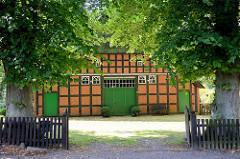 Alte Fachwerkscheune mit Reetdach und Sinnspruch im Fachwerkgebälk; am Eingang hohe Lindenbäume - historische Architektur in Worpswede.