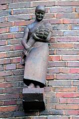 Terrakottafigur, Bauersfrau / Magd mit Ährenbündel an der Fassade des historischen Backsteingebäudes der Kreissparkasse Soltau