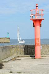 Rotes Molenfeuer / Signalfeuer an der Einfahrt zum Fluthafen, Nassauhafen in Wilhelmshaven; im Hintergrund das grüne Pentdant - ein Segelschiff fährt unter Segeln den Hafen ein.