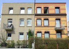 Symmetrische Architektur in der Straße Steenwisch von Hamburg Stellingen; das Gebäude rechts  hat die alte gelbe Klinkerfassade  mit roten Zierbändern, während die linke Fassade  eintönig modernisiert wurde.