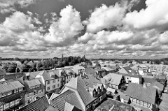 Blick über die Dächer von Soltau - dichte weiße Wolken am Himmel; schwarz-weiß-Aufnahme.