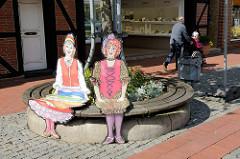 Runde Sitzbank  um eine Baumscheibe in der Fußgängerzone der Marktstraße in Soltau; zwei bunte Frauenfiguren laden zum Sitzen ein.