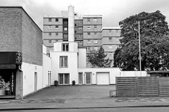 Architektur in Wilhelmshaven -- kkubisches Einzelhaus am Parkplatz, weißer Fassade - dahinter ein mehrstöckiger Wohnblock.