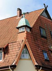 Hausdach / Krüppelwalmdach mit kupfergedecktem Eckturm - Pferdeköpfe als Giebelschmuck; Architektur in Soltau.