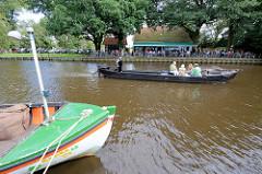 Ein Torfkahn mit Touristen an Bord startet zu seiner Rundfahrt durch das Teufelsmoor auf der Hamme bei Worpswede; am Ufer ein Café / Restaurant mit Biergarten.